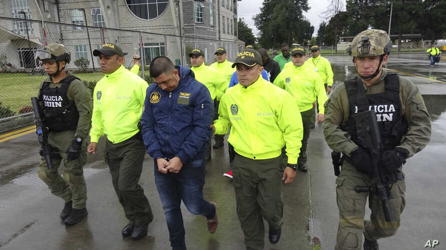 FILE - This undated photo released by Colombia's National Police shows officers escorting a man whom police identified as Ecuadorean drug trafficker Washington Edison Prado after his April 2017 arrest on an indictment by a Florida federal court. Colo