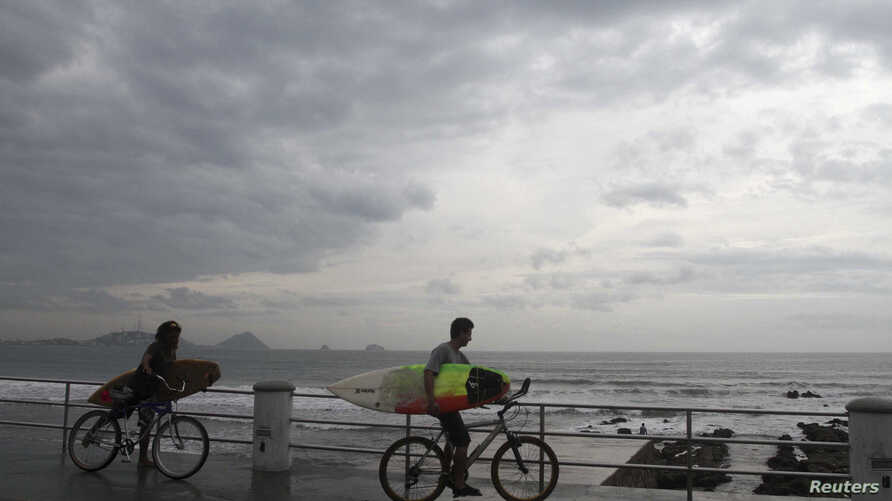 Surfers arrive at El Camaron beach before paddling out into the surf generated by tropical storm Sonia in Mazatlan, in the Mexican state of Sinaloa November 3, 2013.