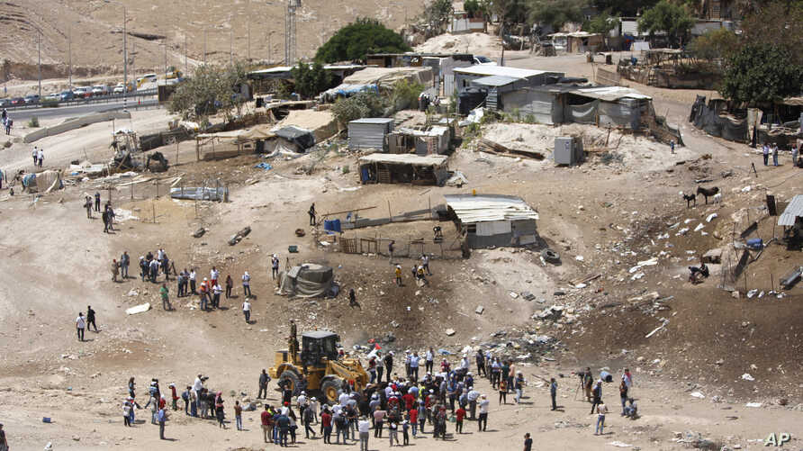 Palestinians gather around a bulldozer in Khan al-Ahmar, Wednesday, July 4, 2018. Israeli police scuffled with activists at a West Bank Bedouin community ahead of its planned demolition.
