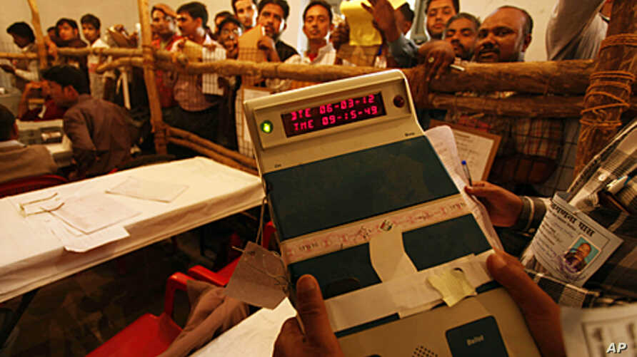 An election official shows an electronic voting machine to poll agents at a counting station in Lucknow, India, March 6, 2012.