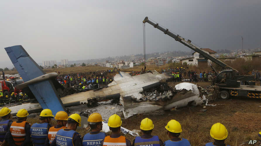 FILE- In this Monday, March 12, 2018 file photo, Nepalese rescuers and police are seen near the debris after a passenger plane from Bangladesh crashed at the airport in Kathmandu.