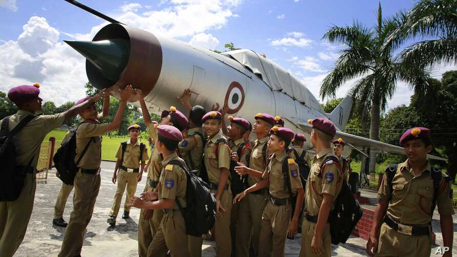 Students gather by an inactive fighter aircraft on display at a Sainik School, or military school, in Goalpara, in the northeastern Indian state of Assam, August 8, 2014..
