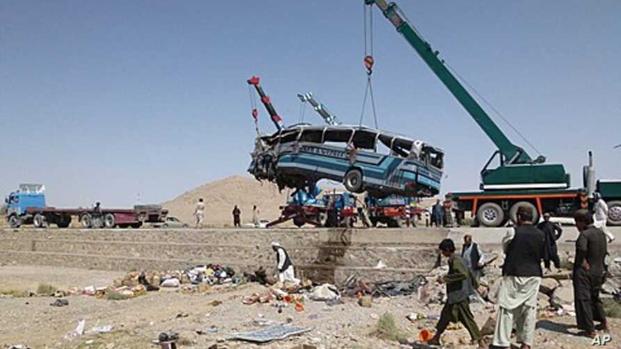A crane lifts a bus that skidded off the road on Kabul-Kandahar highway in Dama district south of Kabul, Afghanistan, August 20, 2011