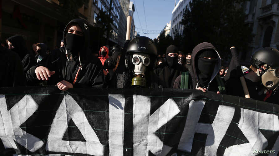 Masked youths take part in an anniversary rally marking the shooting of a 15-year-old student by a policeman in 2008, in Athens, Dec. 6, 2014.