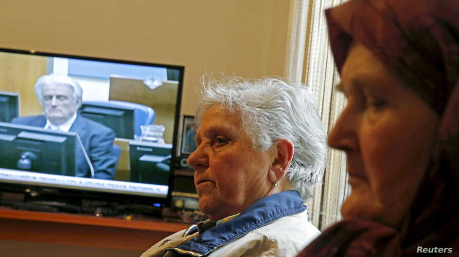Sajma Smajlovic (R) and Vasva Smajlovic watch on television the genocide trial of former Bosnian Serb leader Radovan Karadzic over the 1995 Srebrenica massacre as he appears before the U.N. tribunal in The Hague, as they gather at Smajlovic's house i
