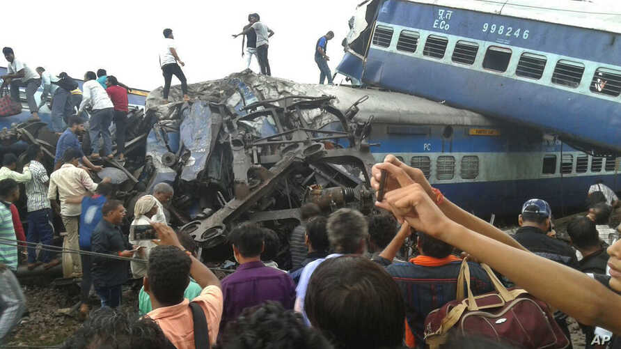 Railway police and local volunteers look for survivors in the upturned coaches of the Kalinga-Utkal Express after an accident near Khatauli, in the northern Indian state of Uttar Pradesh, Aug. 19, 2017.