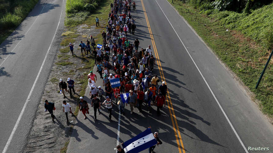 Central American migrants, part of a caravan trying to reach the U.S., walk along the road as they continue their journey, in Ciudad Hidalgo, Mexico, Oct. 26, 2018.