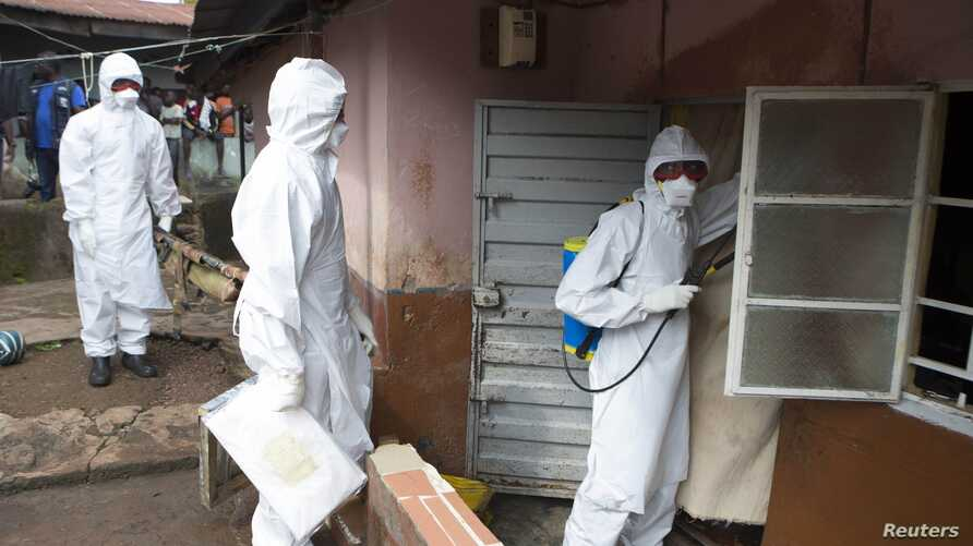 A burial team wearing protective clothing prepare to enter the home a person suspected of having died of the Ebola virus, in Freetown, September 28, 2014.