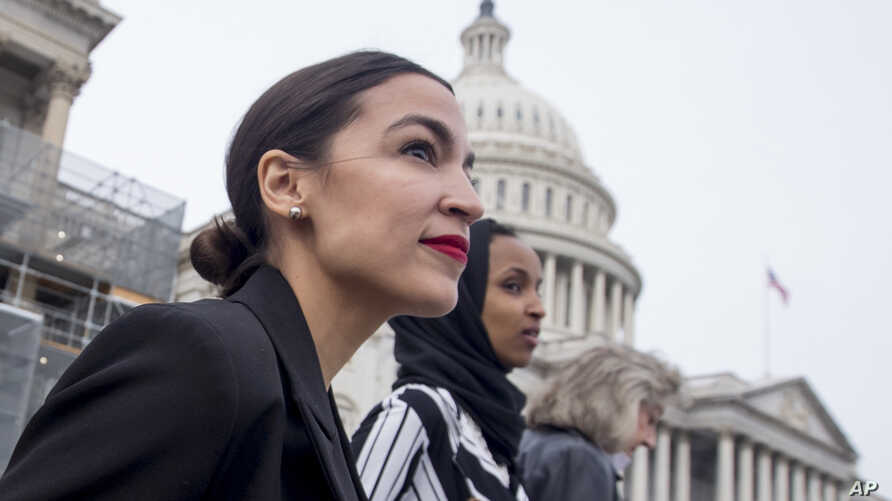 FILE - Rep. Alexandria Ocasio-Cortez, left, and D-N.Y., Rep. Ilhan Omar, D-Minn., center, walk down the House steps to take a group photograph of the House Democratic women members of the 116th Congress on the East Front Capitol Plaza on Capitol Hill
