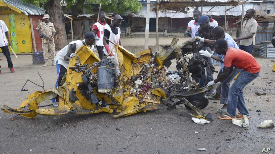 People inspect a damaged tricycle at the site of a bomb explosion, caused by a female suicide bomber in a market, in Maiduguri, Nigeria, July 31, 2015.