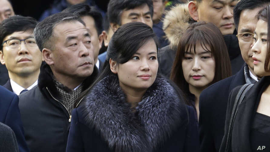 North Korean Hyon Song Wol, center, head of a North Korean art troupe, watches while South Korean protesters stage a rally against her visit in front of Seoul Railway Station in Seoul, South Korea, Monday, Jan. 22, 2018.