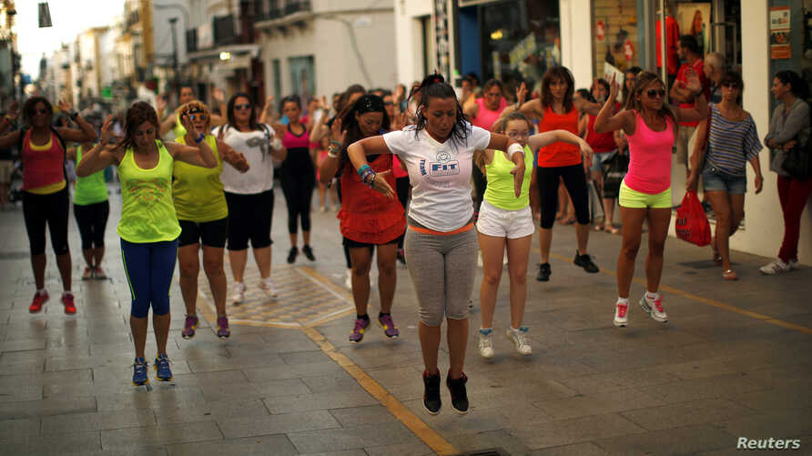 Youths take part in a Zumba exercise class held along the La Bola street in the Andalusian city of Ronda, near Malaga, southern Spain July 11, 2013.    REUTERS/Jon Nazca (SPAIN  - Tags: SOCIETY) - RTX11KFI