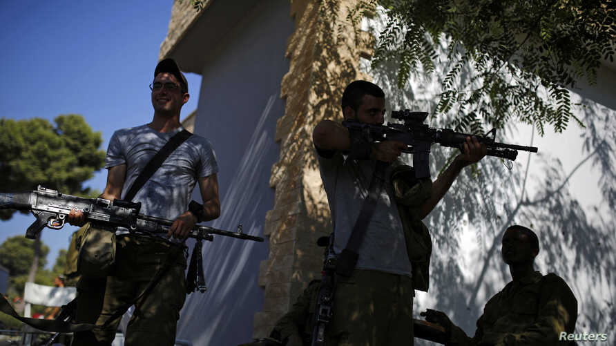 An Israeli soldier checks his weapon near the border with Gaza, August 6, 2014.