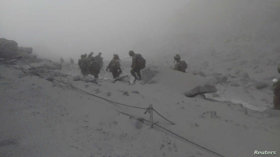 Japan Self-Defense Force (JSDF) soldiers conduct rescue operations near the peak of Mount Ontake, which erupted September 27, 2014 and straddles Nagano and Gifu prefectures, central Japan, in this handout photograph released by the Joint Staff of the