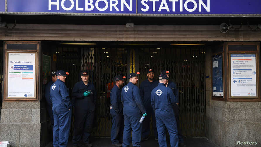 London Underground workers stand outside Holborn Station, that was closed following a fire alert, in central London Britain, Aug. 15, 2017.