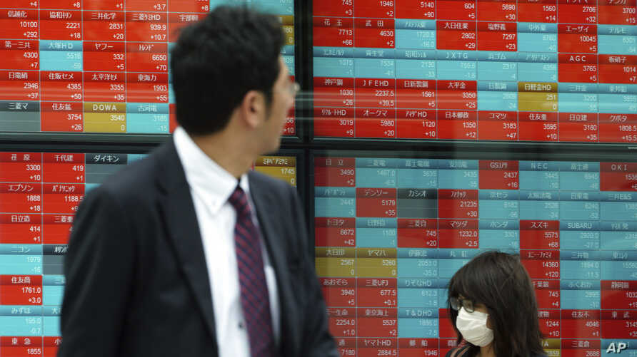 People walk past an electronic stock board showing Japan's Nikkei 225 index at a securities firm in Tokyo, Nov. 7, 2018. Asian shares were mostly higher Wednesday, following the U.S. midterm elections.