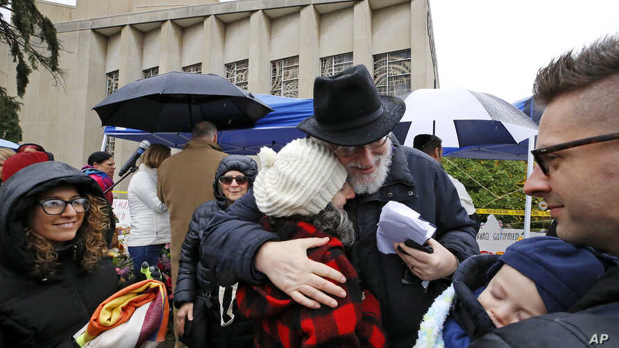 Rabbi Chuck Diamond, center, a former rabbi at the Tree of Life synagogue, hugs a woman after leading a Shabbat service outside Tree of Life, Nov. 3, 2018, in Pittsburgh. On Oct. 27, 11 people were killed and six wounded when a gunman attacked them i