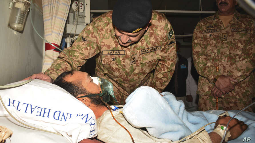 Pakistan's Lt. Gen. Zafar Iqbal Malik enquires about the health of a Kashmiri villager injured by Indian firing, during a hospital visit in Muzaffarabad, Pakistan, Nov. 24, 2016. Pakistan's air force chief has warned arch-rival India against escalati