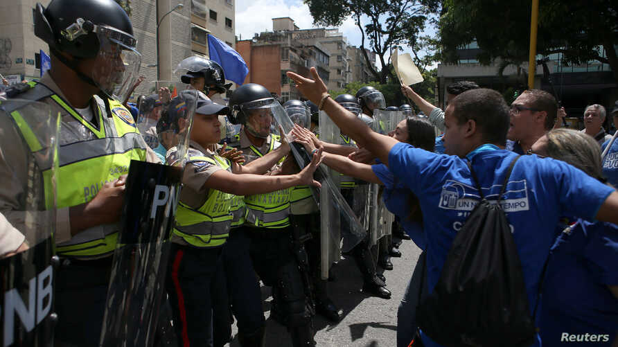 Supporters of Venezuela's opposition (R) face riot police officers who are blocking a street, as they take part in a rally to demand a referendum to remove Venezuela's President Nicolas Maduro, in Caracas, Venezuela, Sept. 16, 2016.