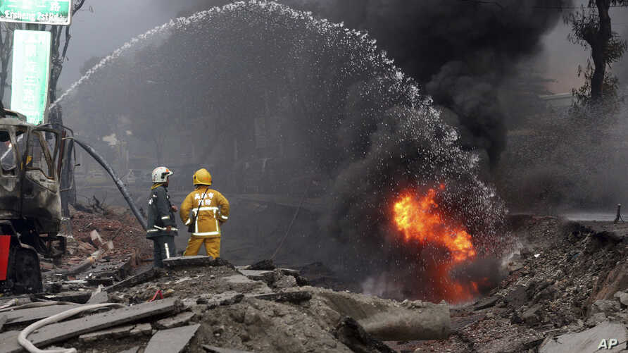 Firemen put out fire on the part of a destroyed street as fire continue to burn following multiple explosions from an underground gas leak in Kaohsiung, Taiwan, Aug. 1, 2014.