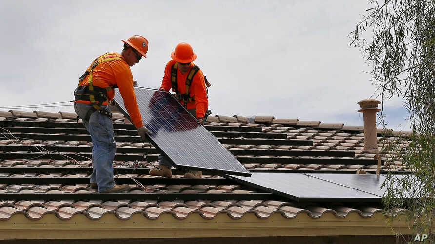 Electricians install solar panels on a roof for Arizona Public Service company in Goodyear, Arizona, July 28, 2015.