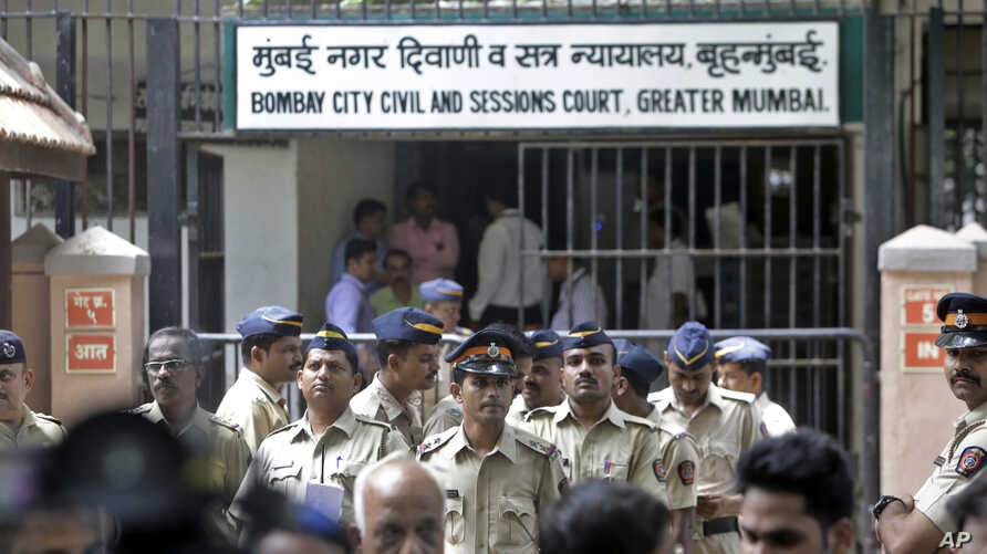 Indian police officials stand guard outside the sessions court complex in Mumbai, India, Thursday, Sept. 7, 2017. An Indian court has sentenced two men to death and another two to life in prison for a series of bombings that killed 257 in Mumbai in 1