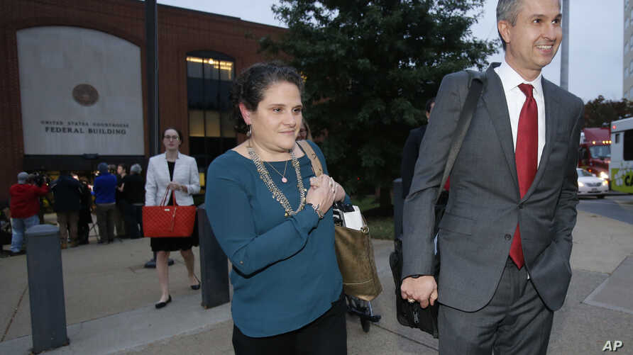 University of Virginia administrator Nicole Eramo leaves federal court with her attorney Tom Clare, right, after closing arguments in her defamation lawsuit against Rolling Stone magazine in Charlottesville, Va., Tuesday, Nov. 1, 2016. A jury ruled i