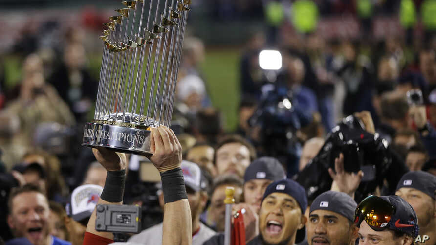 A player holds up the championship trophy after defeating the St. Louis Cardinals in Game 6 of baseball's World Series Wednesday, Oct. 30, 2013.