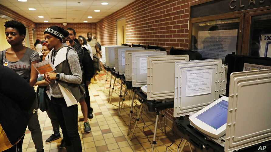 Voters wait in line on election day next to unused machines as the precinct switched over to paper ballots after a judge ordered the polling location to remain open until 10 p.m., in Atlanta, Tuesday, Nov. 6, 2018.