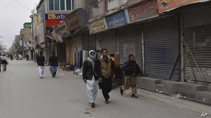 People walk past shops closed because of a strike called to condemn the death of a prominent Pashtun rights activist, in Quetta, Pakistan, Feb. 4, 2019. Pakistan has ordered an investigation into the death of prominent Pashtun rights activist Arman L
