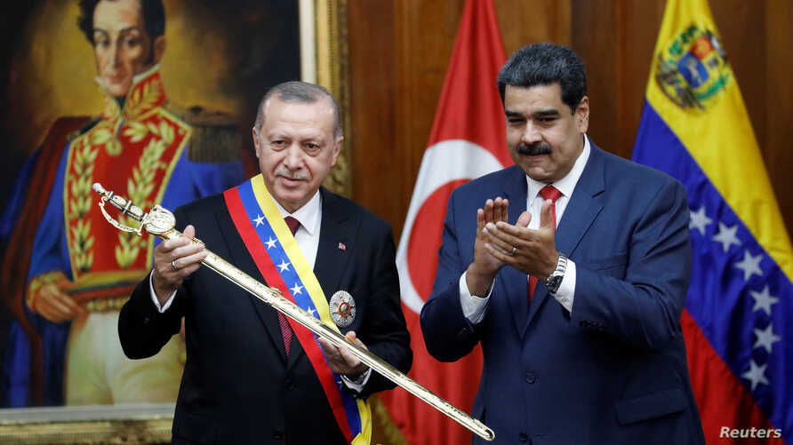 Turkish President Recep Tayyip Erdogan holds a replica of the sword of national hero Simon Bolivar, next to Venezuela's President Nicolas Maduro, during an agreement-signing ceremony between Turkey and Venezuela at Miraflores Palace in Caracas, Venez...