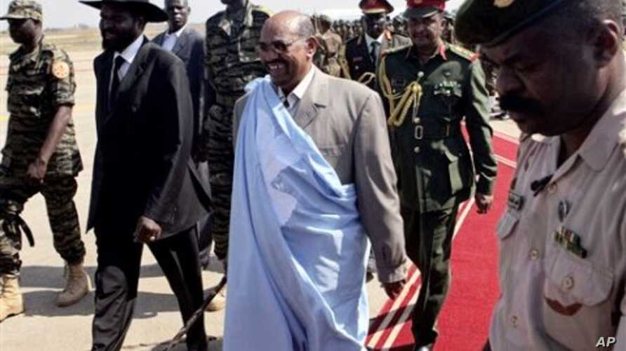 The President of the Republic of Sudan Omar al-Bashir, center, is escorted by Salva Kiir Mayardit, the Vice President of the Republic of Sudan, left,as he arrives at the airport in the southern Sudanese capital of Juba, 4 Jan 2011.