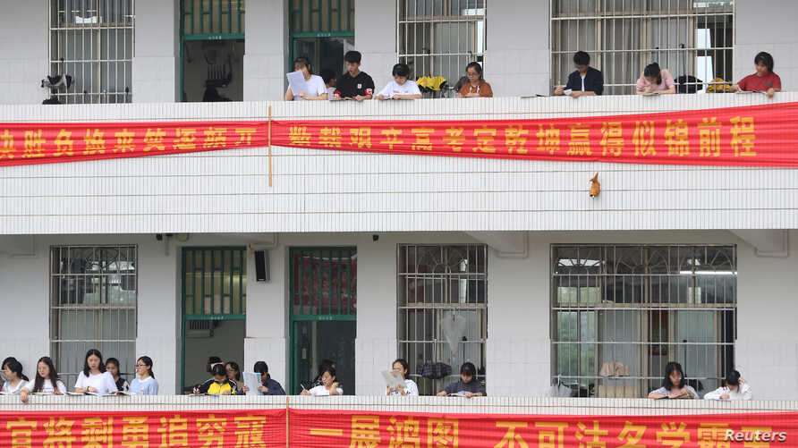Students study along corridors at a high school ahead of the annual national college entrance examination, in Hengyang, Hunan province, China, June 3, 2018. In nearby Leiyang, parents protested a plan to move students from overcrowded schools.