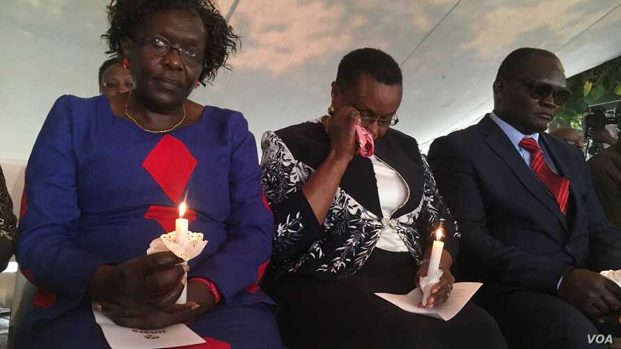 A survivor (center) of the Aug. 7, 1998, U.S. embassy bomb attack in Nairobi, Kenya is seen overwhelmed by emotions at a memorial park in the country's capital, where hundreds gathered Aug. 7, 2018, to remember the victims of the al-Qaida attack 20 y