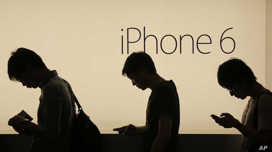 People wait to buy the new Apple iPhone 6 and 6 Plus devices outside an Apple store in Hong Kong, Sept. 19, 2014.