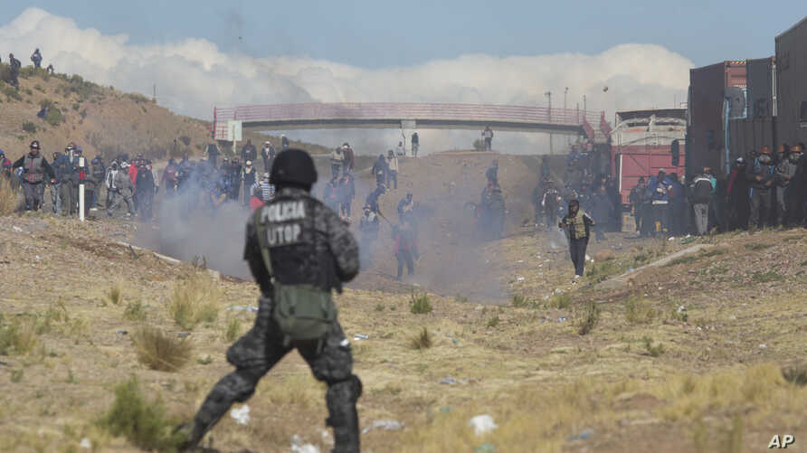 Independent miners clash with the police as they run from clouds of tear gas during protests in Panduro, Bolivia, Thursday, Aug. 25, 2016.