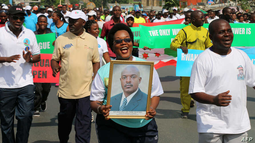 FILE - A woman holds up a picture of Burundi's President Pierre Nkurunziza during a rally in Bujumbura on May 14, 2016, commemorating the one-year anniversary of the failed attempt of a government coup.