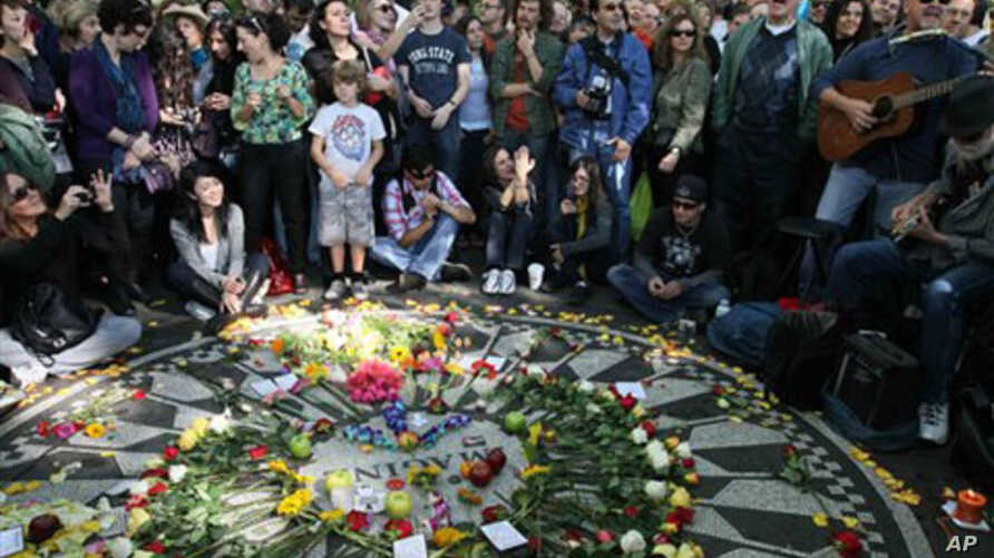 People sing as they gather around the Imagine mosaic in Strawberry Fields in New York's Central Park, 09 Oct 2010, the day that would have been John Lennon's 70th birthday
