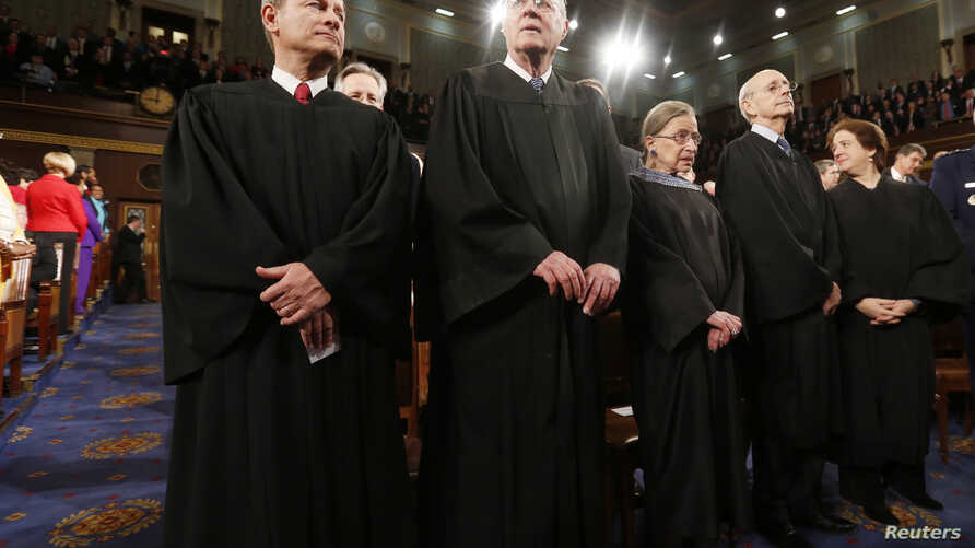 U.S. Supreme Court Chief Justice John Roberts (L) stands with fellow Justices Anthony Kennedy (2nd from L), Ruth Bader Ginsburg, Stephen Breyer and Elena Kagan (R) prior to President Barack Obama's State of the Union speech on Capitol Hill in Washing...