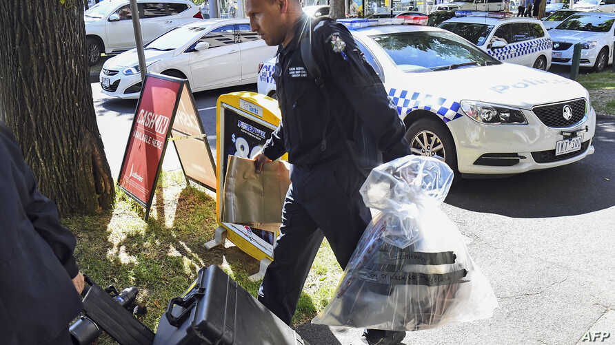 A Victoria police forensics officer carries items to be loaded into a trailer outside the Italian Consulate in Melbourne, Jan. 9, 2019. Australian police are investigating the delivery of suspicious packages sent to foreign embassies and consulates i