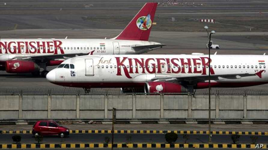 A car moves past Kingfisher Airlines aircraft parked at the airport in New Delhi February 21, 2012.