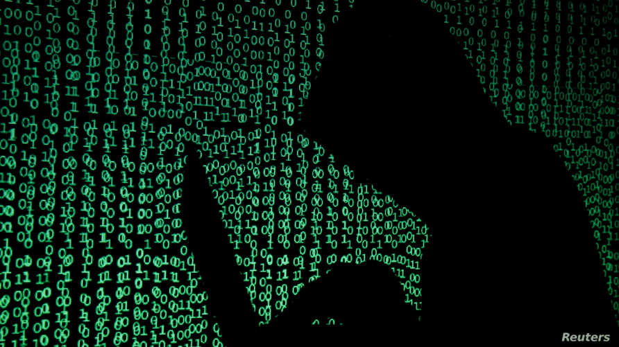 FILE - A hooded man holds a laptop computer as cybercode is projected on him in this photo illustration.
