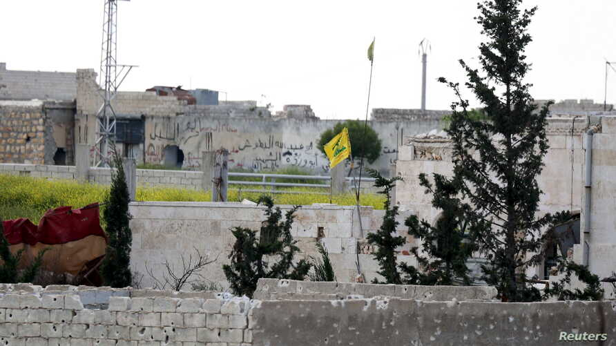A Hezbollah flag flutters in a government-controlled area, as seen from the rebel-controlled area of Karm al-Tarab frontline, near Aleppo international airport, April 22, 2015.