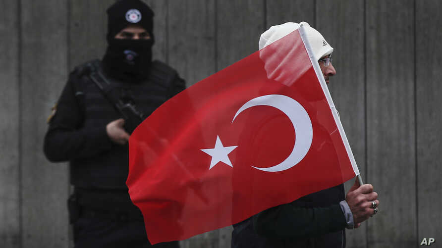 A man with a Turkish flag walks past a Turkish police officer guarding the scene, during a memorial outside the Reina club following the New Year's day attack, in Istanbul, Turkey, Jan. 3, 2017.