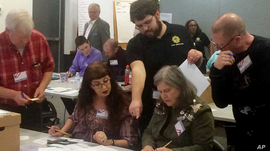 Election officials in Newport News, Virginia, examine ballots that a computer failed to scan during a recount for a House of Delegates race on Dec. 19, 2017.