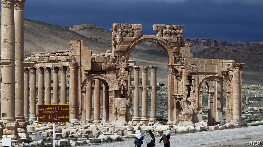 A picture taken on March 14, 2014 shows Syrian citizens walking in the ancient oasis city of Palmyra, 215 kilometres northeast of Damascus.