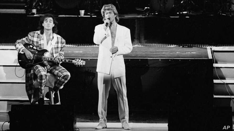 FILE - George Michael and Andrew Ridgeley of the British group WHAM! perform during a concert in Peking, China, April 7, 1985. Michael, who rocketed to stardom with WHAM! and went on to enjoy a long and celebrated solo career lined with controversies