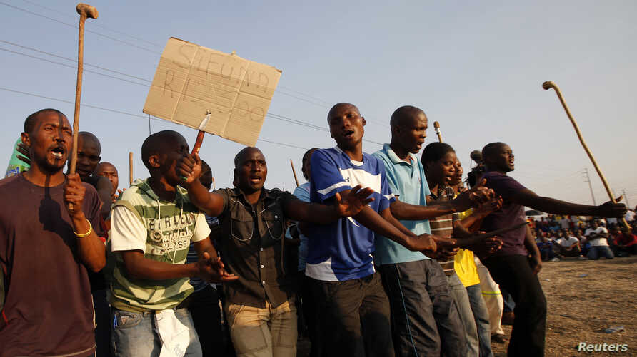 Striking platinum miners are seen gathered at Lonmin's Marikana mine in South Africa August 29, 2012.
