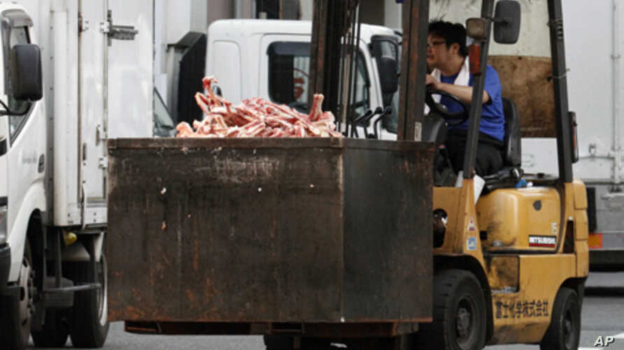 A worker operates a forklift, carrying a container loaded with a pile of bones of beef, at a wholesale meat market in Tokyo, July 12, 2011