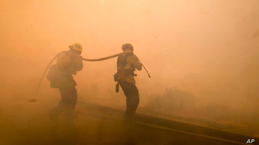 Firefighters battle a fire along the Ronald Reagan (118) Freeway in Simi Valley, California, Nov. 12, 2018.